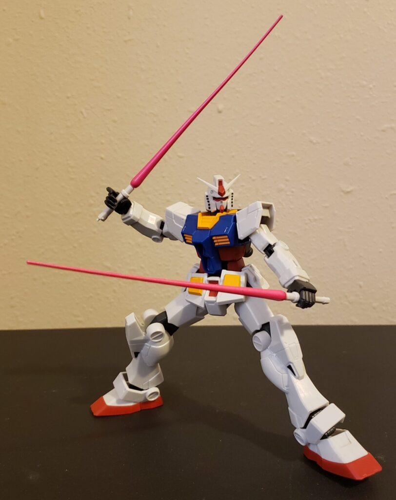 The Gundam adopts a wide stance, twin sabers at the ready.